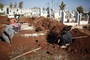 A boy watches men dig graves for future casualties of Syria's civil conflict, at Sheikh Saeed cemetery in Azaz city